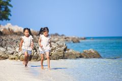 Two asian child girls having fun to play and run on beach together in summer vacation. Two cute asian child girls having fun to play and run on beach together in stock image