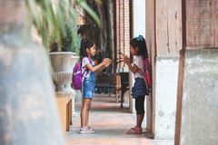 Two cute asian child girls with school bag playing together after school in the school royalty free stock image