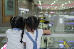 Two asian child girls waiting for boarding in the airport together. Two cute asian child girls waiting for boarding in the airport together royalty free stock images