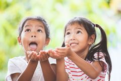 Two cute asian child girls waiting candies falling from the sky. With fun and excited royalty free stock photos