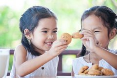 Two cute asian little child girls are eating cookies with milk stock images