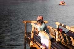 Two cute asian little child girls fun to feed fish. Two cute asian little child girls having fun to feed and give food to fish in the lake together with sunlight Royalty Free Stock Images