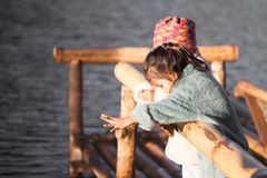 Two cute asian little child girls fun to feed fish. Two cute asian little child girls having fun to feed and give food to fish in the lake together with sunlight Stock Images