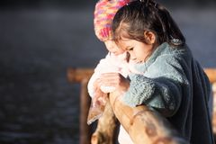 Two cute asian little child girls having fun to feed fish. Two cute asian little child girls having fun to feed and give food to fish in the lake together with Royalty Free Stock Images