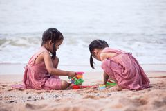 Two cute asian little child girls having fun to play with sand stock images