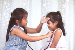 Two cute asian little child girls playing doctor and patient Royalty Free Stock Photo