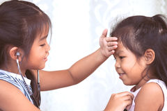 Two cute asian little child girls playing doctor and patient Stock Photo