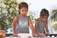 Two cute asian little child girls prepare a dough for baking Stock Photos