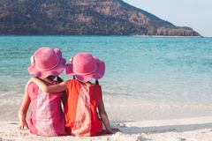 Two asian little child girls sitting and hugging each other  on the beach near the beautiful sea in summer vacation stock photography