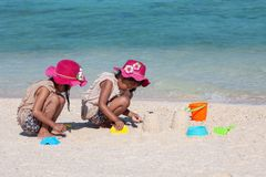 Two asian little child girls sitting and playing with sand together on the beach near the beautiful sea in summer vacation royalty free stock image