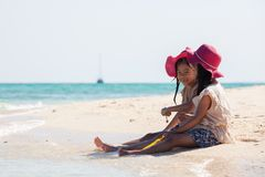 Two asian little child girls sitting and playing with sand together on the beach near the beautiful sea in summer vacation royalty free stock photography