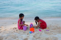 Two asian little child girls sitting and playing with sand together on the beach near the beautiful sea in summer vacation royalty free stock images