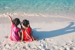 Two asian little child girls sitting and playing together on the beach near the beautiful sea in summer vacation royalty free stock photos