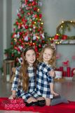Two cute awesome girls sisters celebrating New Year Christmas close to xmas tree full of toys in stylish dresses with candies Stock Image