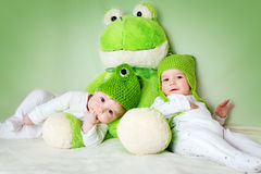 Two cute babies lying in frog hats with a soft toy. Two cute six month old babies lying in frog hats with a soft toy royalty free stock photography