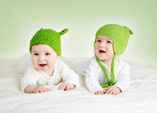 Two cute babies lying in frog hats on spft blanket. Two cute six month old babies lying in frog hats on soft blanket stock photos