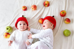 Two cute babies lying in hats on soft blanket with apples Royalty Free Stock Photo