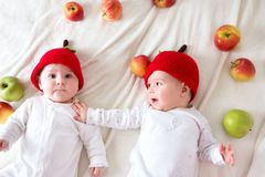Two cute babies lying in hats on soft blanket with apples. Two cute six month old babies lying in hats on soft blanket with apples stock photography