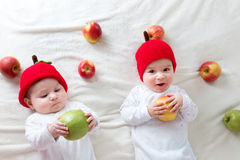 Two cute babies lying in hats on soft blanket with apples Stock Images