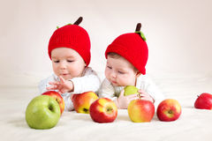 Two cute babies lying in hats on soft blanket with apples. Two cute six month old babies lying in hats on soft blanket with apples royalty free stock image