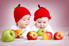 Two cute babies lying in hats on soft blanket with apples. Two cute six month old babies lying in hats on soft blanket with apples royalty free stock photo