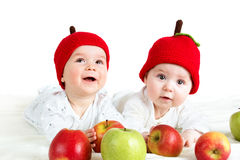 Two cute babies lying in hats on soft blanket with apples. Two cute six month old babies lying in hats on soft blanket with apples royalty free stock photography