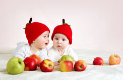 Two cute babies lying in hats on soft blanket with apples Stock Image