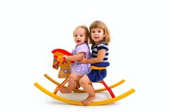 Two cute babies riding on a toy horse Stock Photo