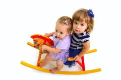 Two cute babies riding on a toy wooden horse  Royalty Free Stock Photography