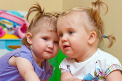 Two cute baby girls. Portrait of two cute baby girls with pigtails playing indoors Royalty Free Stock Photo