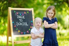 Two cute being unhappy about going to school. Two adorable sisters feeling unhappy about going back to school Stock Photography