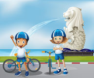 Two cute bikers standing in the front of the Merlion Royalty Free Stock Photography