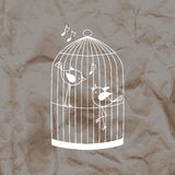 Two cute birds in a cage on a kraft paper background. Stock Image
