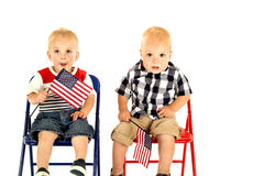 Two cute blond boys holding American flags sitting Stock Image