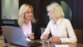Two cute blondes discuss working issues. Two girls are sitting at the table in the office. They are looking at something in the laptop and are discussing it stock video footage