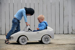 Two Cute boy plays with a toy car. And a race prize for a rural farmstead in a hot summer royalty free stock photos
