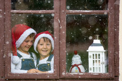 Two cute boys, brothers, looking through a window, waiting for S Stock Image