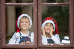 Two cute boys, brothers, looking through a window, waiting for S Royalty Free Stock Image