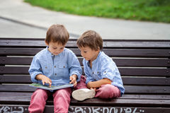 Two cute boys, brothers, read a book in the park, sitting on ben Royalty Free Stock Photography
