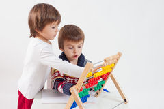 Two cute boys, learning to count and math. Playing at home, isolated on white stock image