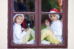 Two cute boys, looking through a window, waiting for Santa Royalty Free Stock Images