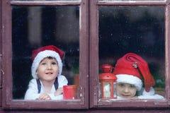 Two cute boys, looking through a window, waiting for Santa Stock Photos