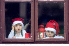 Two cute boys, looking through a window, waiting for Santa Royalty Free Stock Photography