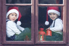 Two cute boys, looking through a window, waiting for Santa Stock Photo
