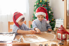 Two cute boys with santa hat, preparing cookies at home, Christm Royalty Free Stock Images