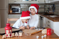 Two cute boys with santa hat, preparing cookies in the kitchen Stock Photography