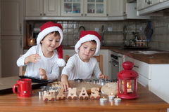 Two cute boys with santa hat, preparing cookies in the kitchen Stock Photo