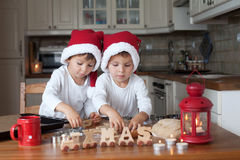 Two cute boys with santa hat, preparing cookies in the kitchen Royalty Free Stock Images