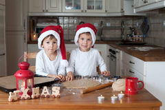 Two cute boys with santa hat, preparing cookies in the kitchen Stock Image