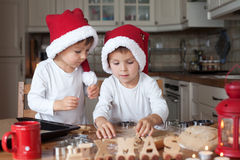 Two cute boys with santa hat, preparing cookies in the kitchen Royalty Free Stock Photo